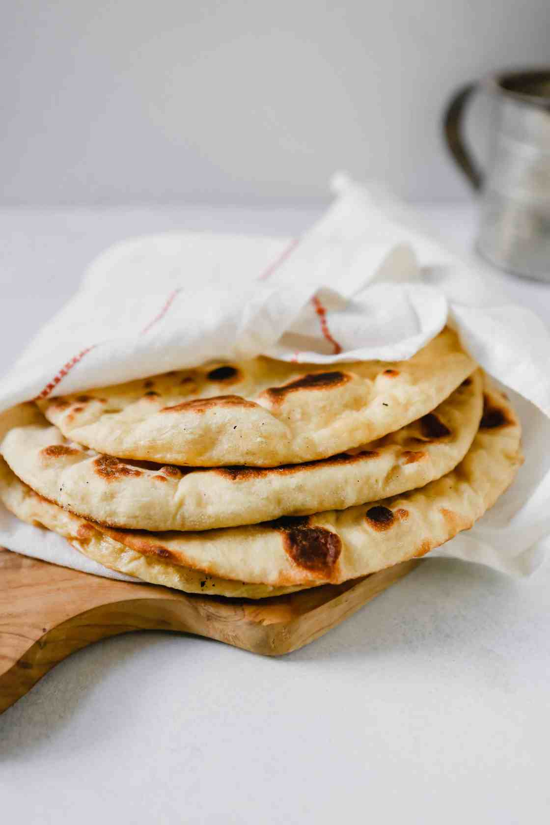 Homemade naan bread wrapped in a white towel