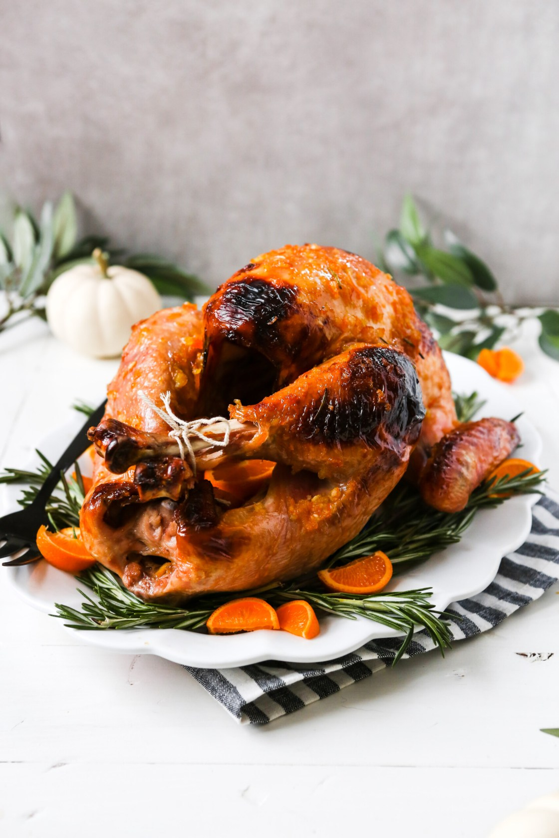 photograph of a whole glazed roast turkey on a large white platter