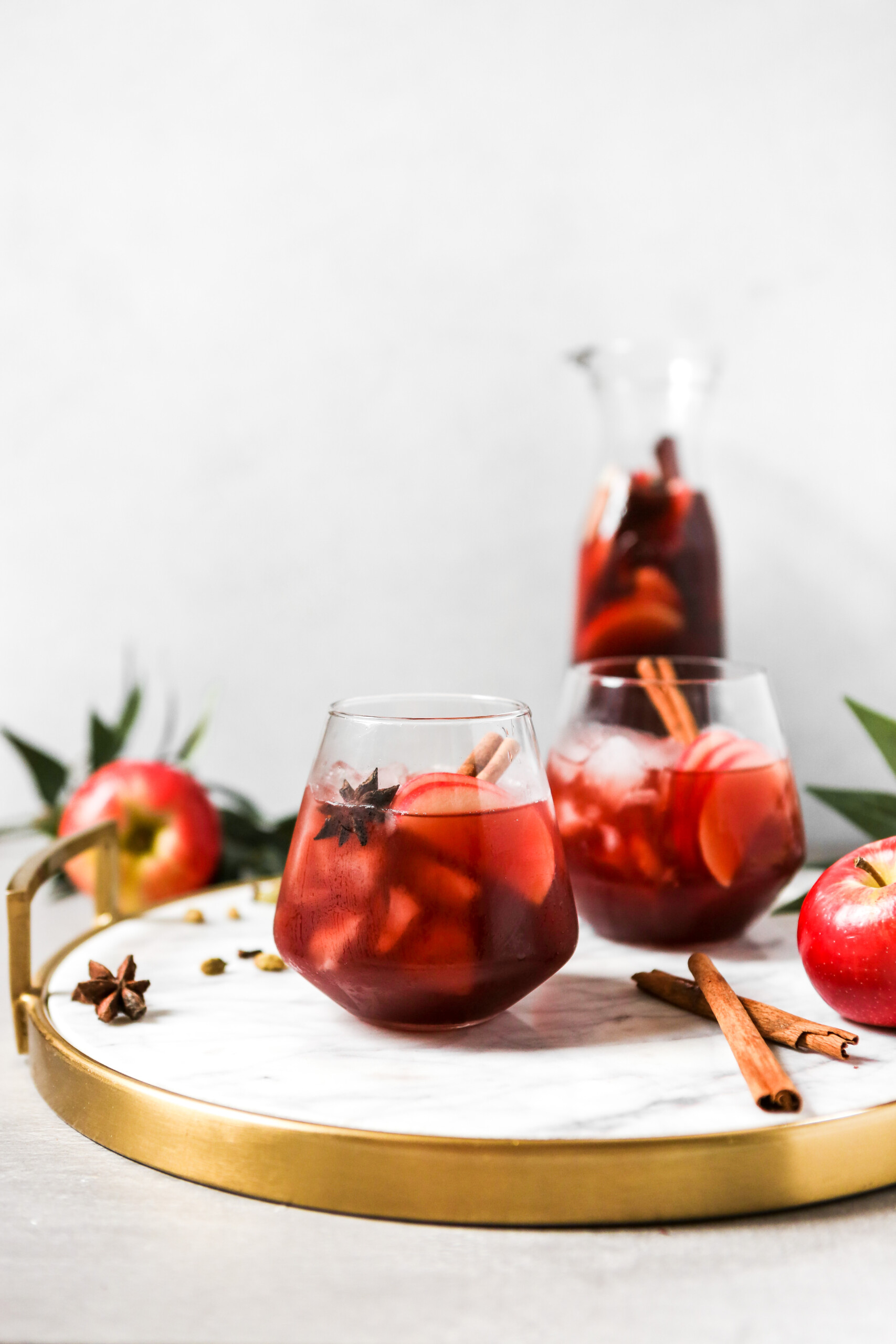 photography of a Red wine apple sangria set on a white marble tray