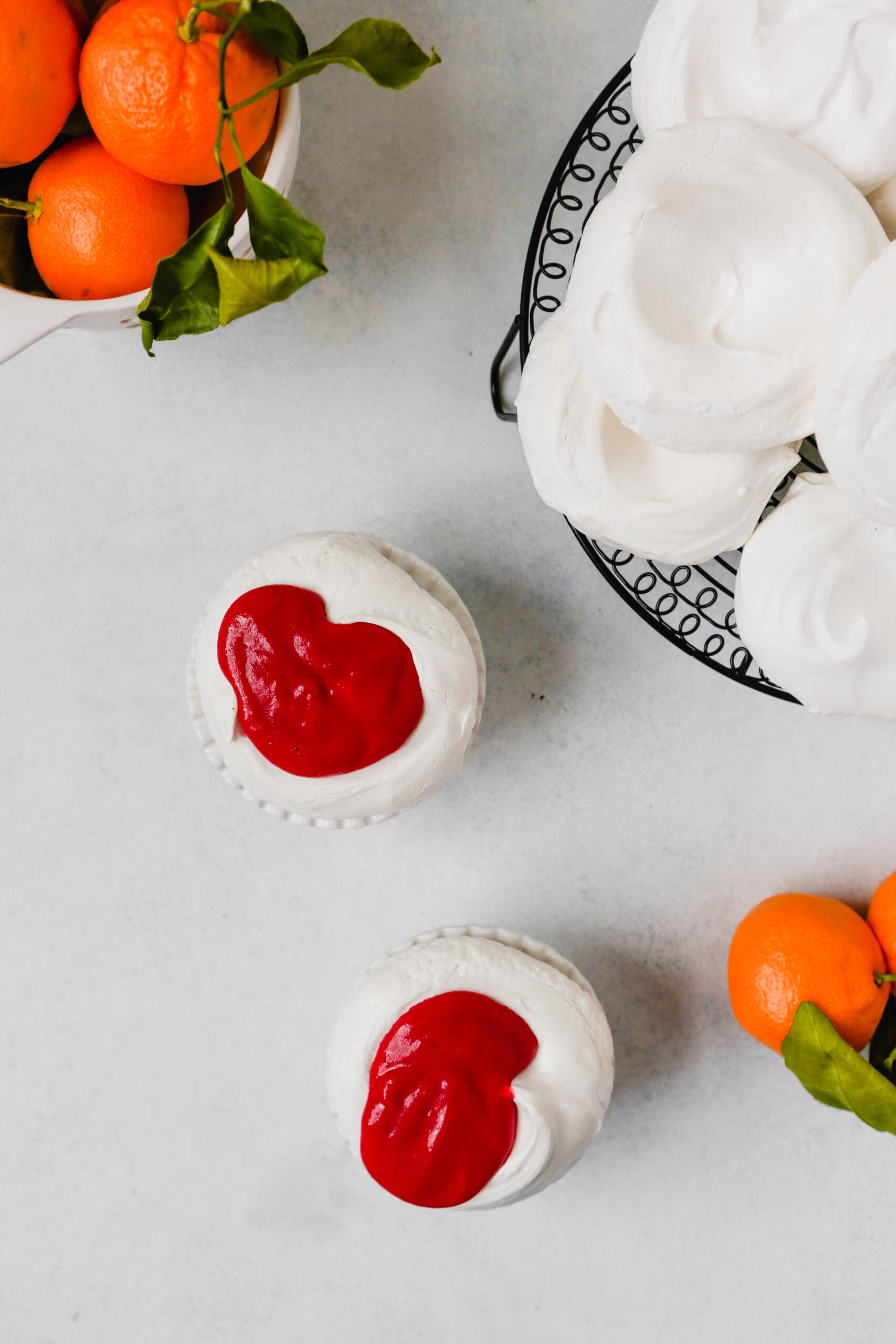 Photography of mini pavlova topped with pink cranberry curd.
