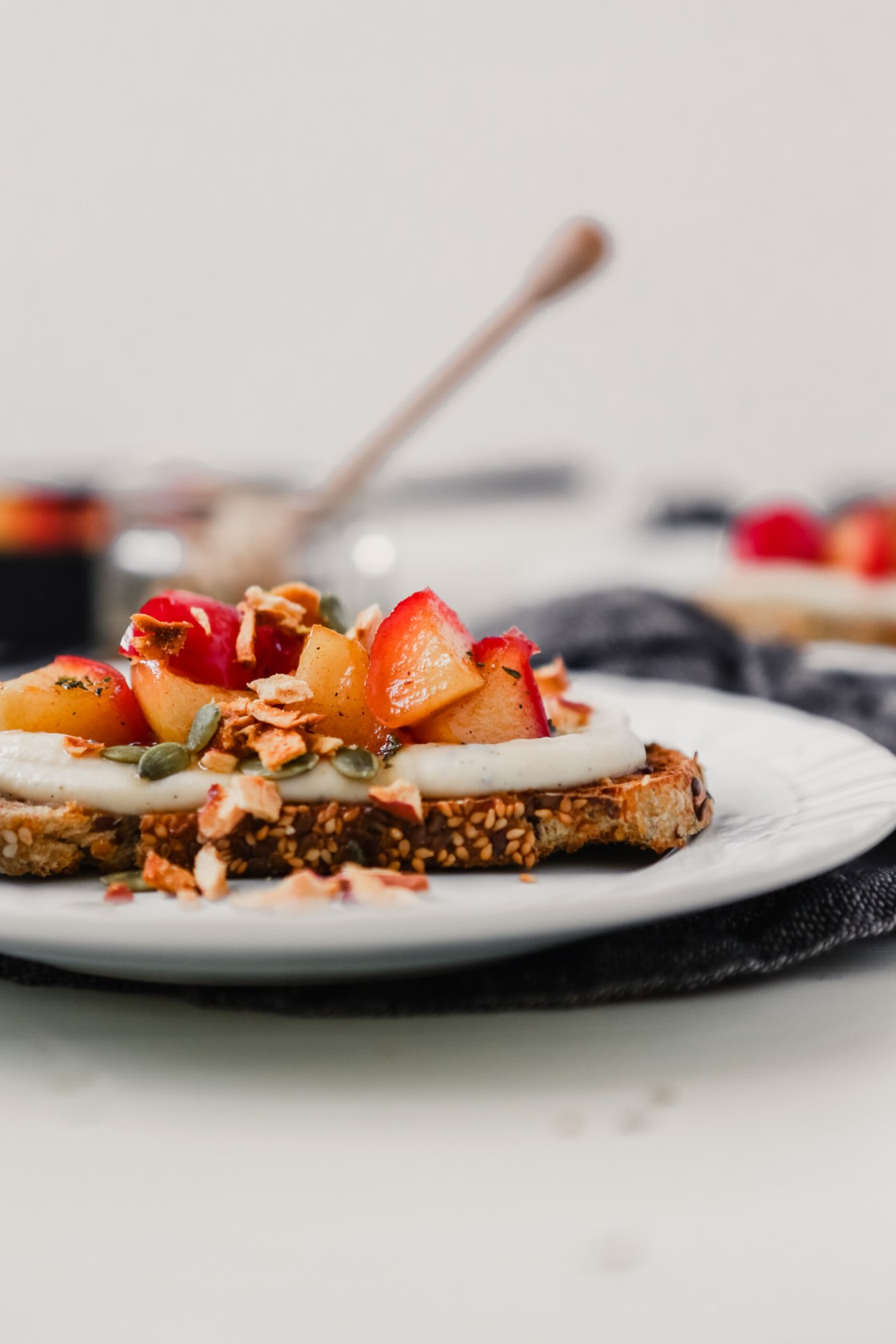 Photograph of wholegrain bread topped with ricotta, sauteed apples, and honey on a white plate