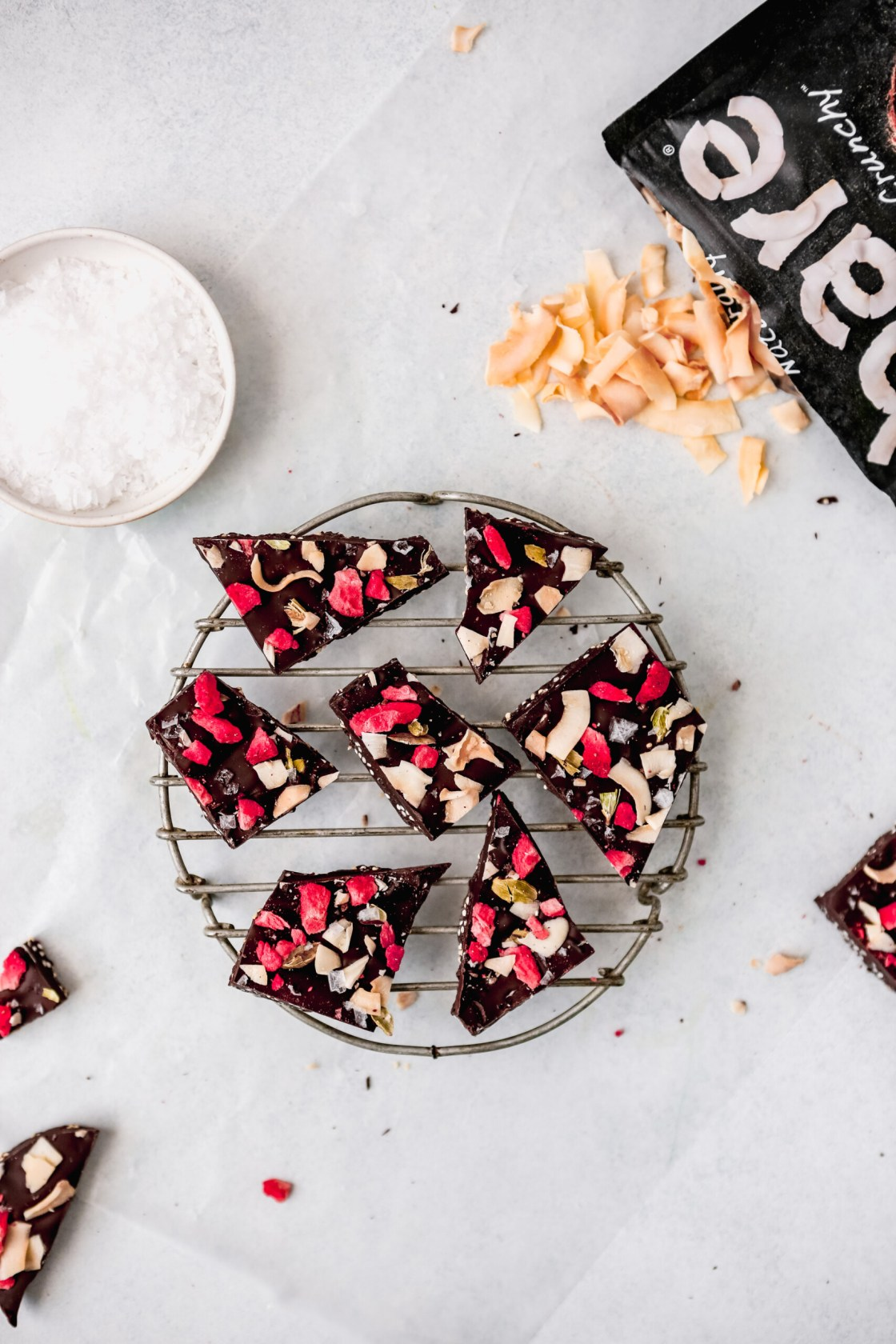 Overhead photograph of dark chocolate coconut bark set on a white table with salt set on a wire rack