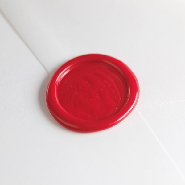 Photo of wax seal in cherry red on white enevlope