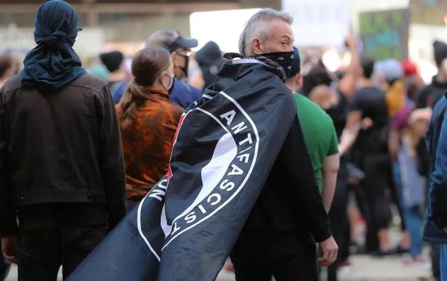 A protester with an antifa flag draped over his shoulders stands at a rally to demand justice for George Floyd and support of the Black Lives Matter movement in Boston on May 31. (Photo by Matthew J. Lee / The Boston Globe via Getty Images)
