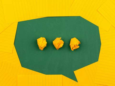 orange sheets of paper lie on a green school board and form a chat bubble with three crumpled papers.