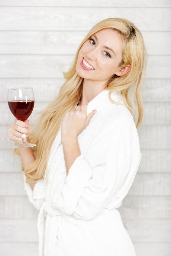 Beautiful young woman in a white robe enjoying a glass of red wine
