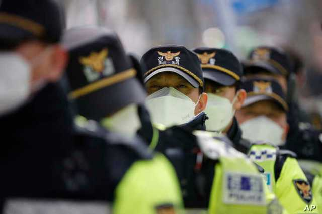 Police officers wearing face masks stand guard during a rally in downtown Seoul, South Korea, Saturday, Feb. 22, 2020. South…