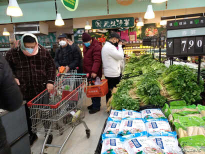FILE PHOTO: People wearing masks shop at a supermarket on the second day of the Chinese Lunar New Year, following the outbreak…