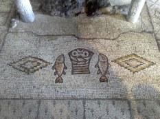 """Piękna mozaika go przedstawia. Wg Mt 14,13-21 jest 5 chlebów i 2 ryby, tu zaś w koszu jedynie 4 chleby. Piątym prawdopodobnie jest chleb eucharystyczny. 2 widoczne """"nogi"""" to ołtarz."""
