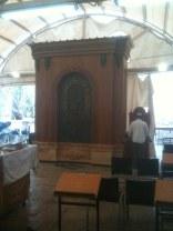 """Współczesna synagoga znajduje się pomiędzy murami, wewnątrz których umieszczono """"cenotaphia"""" Patriarchów. Całość sanktuarium podzielona jest na 2 części: muzułmańską i żydowską. Widzimy tę drugą."""