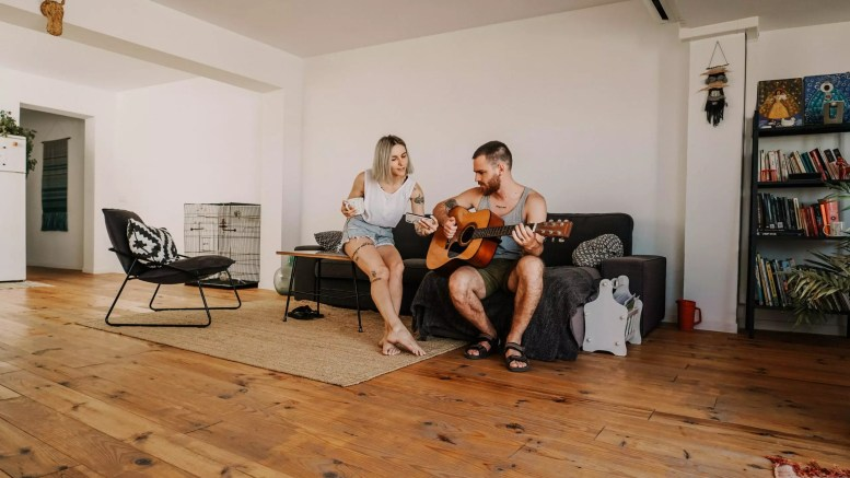 wood flooring man sitting and playing acoustic guitar near woman in living room