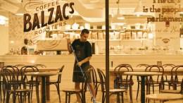 sanitation man mopping floor of Coffee Balzac's roaster