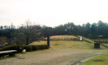 【写真】信楽陶芸の森。火の丘を東側から望む。左手に咲き始めの桜。丘の上に親子。曇り空。