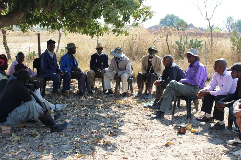 elderly men seated in semi-circle