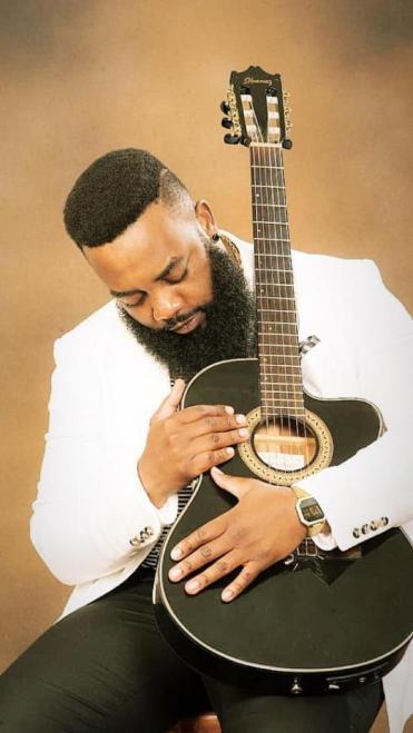 Shammah Musiq holding a guitar