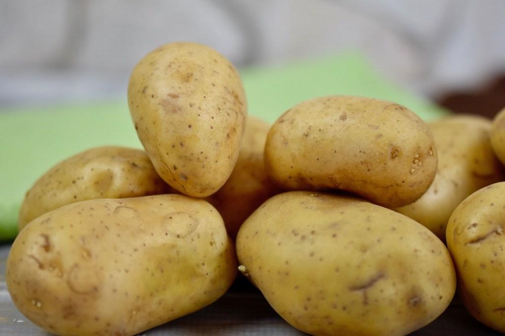 mehrere Kartoffeln mit Schale liegen zusammen