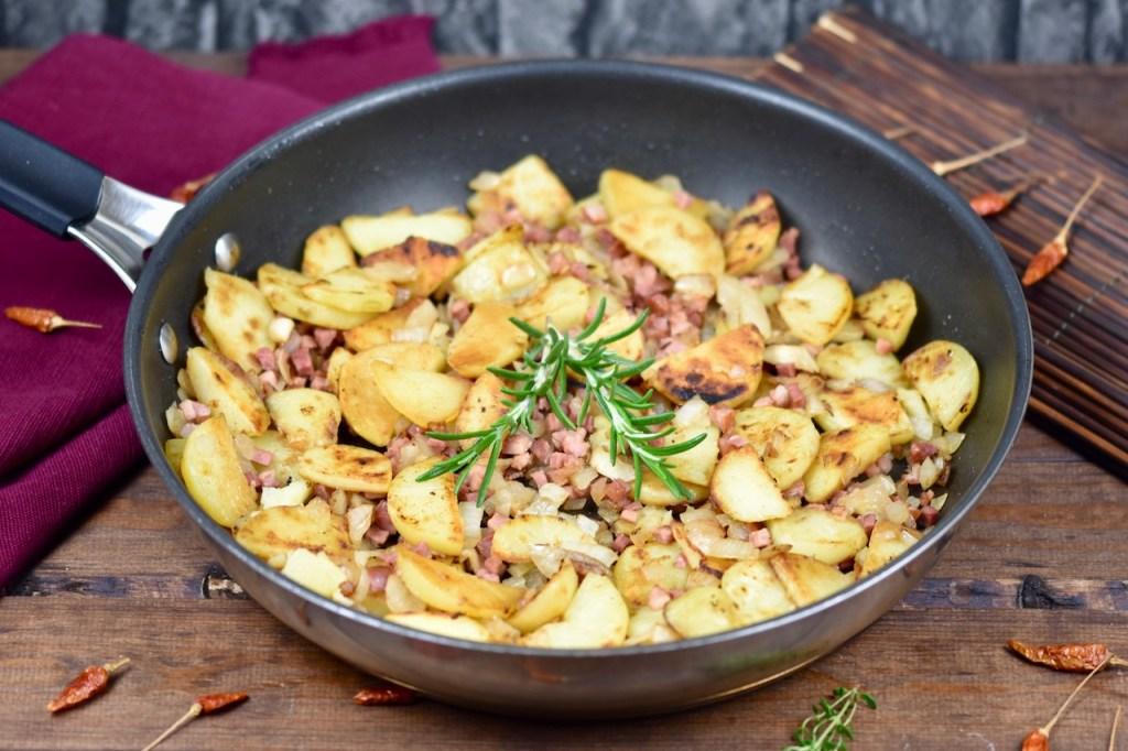 Knusprige Bratkartoffeln mit Speck und Zwiebeln in einer Pfanne, garniert mit Rosmarin