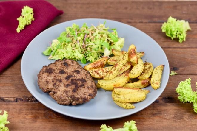 Pljescavica als Tellergericht mit Salat und Kartoffelspalten - auf grauem Teller, der auf einer dunklen Holzplatte steht