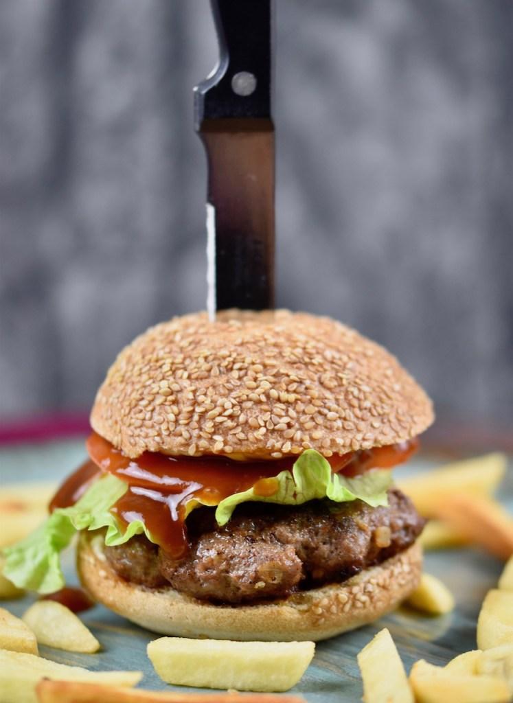 Pljescavica Burger aufgespießt mit einem Messer auf einem bläulichen Teller. Drumherum liegen Pommes frites. Dunkler Hintergrund.