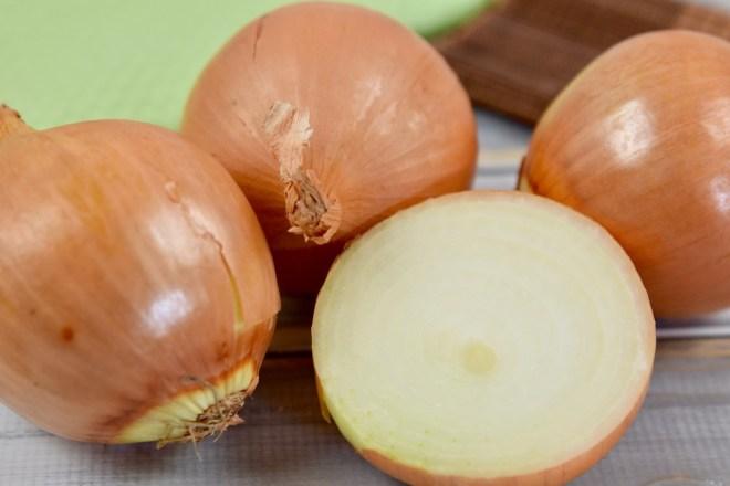 drei gelbe Zwiebeln und eine aufgeschnittene Hälfte, Hintergrund hell