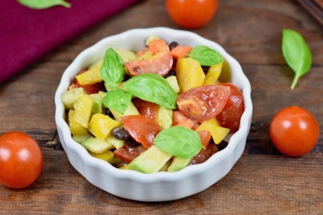 Bunter Avocado-Salat mit Tomaten in weißer Schale. Dekoriert mit Basilikum. Hintergrund dunkel