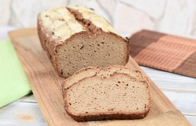 glutenfreies Krustenbrot in Kastenform auf Holzbrett mit 2 angeschnittenen Scheiben. Hintergrund hell.