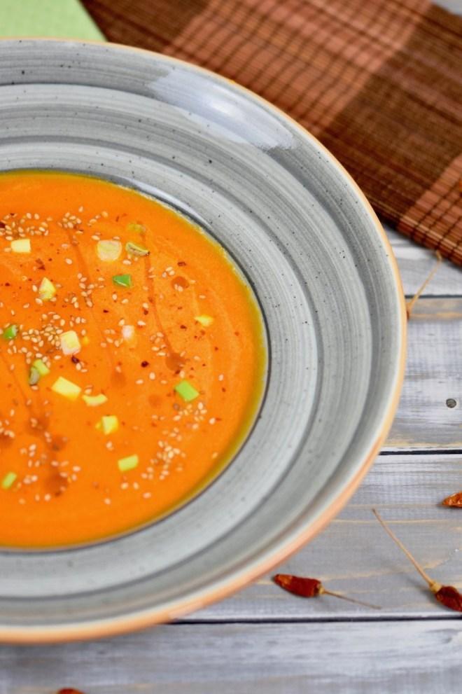 Karottensuppe mit Ingwer und Orange in grauem Teller. Garniert mit Sesamsamen, Sesamöl und Frühlingszwiebeln. Der Teller ist nur halb zu sehen. Hintergrund hell.