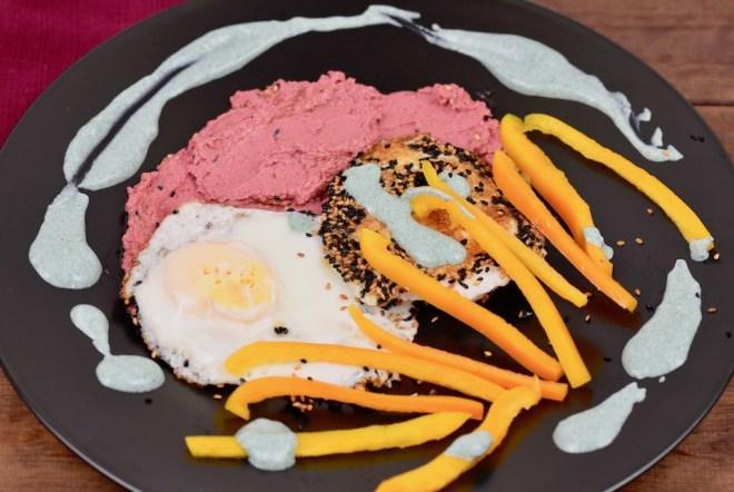Knusprige Spiegeleier mit einer Kruste aus Sesam und Schwarzkümmelsamen mit pinkem Rote Beete Hummus und grüner Tahini-Sauce. Dazu gibt es gelbe Paprikastreifen Angerichtet ist alles auf einem schwarzen Teller.