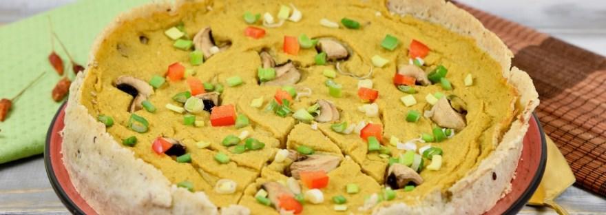 Glutenfreie Quiche mit Pilzen garniert mit Champignons, Paprika und Frühlingszwiebeln. Hintergrund hell.