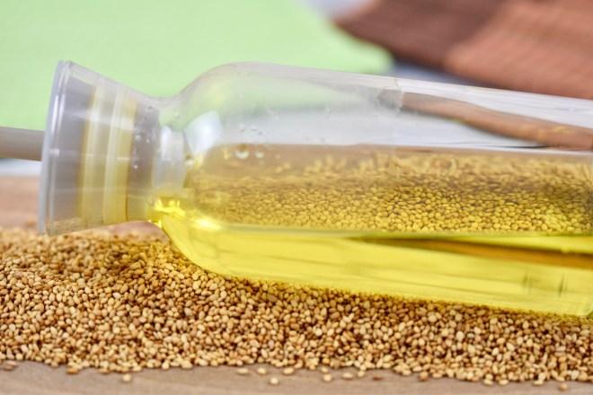 Sesamöl in Glasflasche. Die Flasche liegt auf einem Bett von Sesamkörnern
