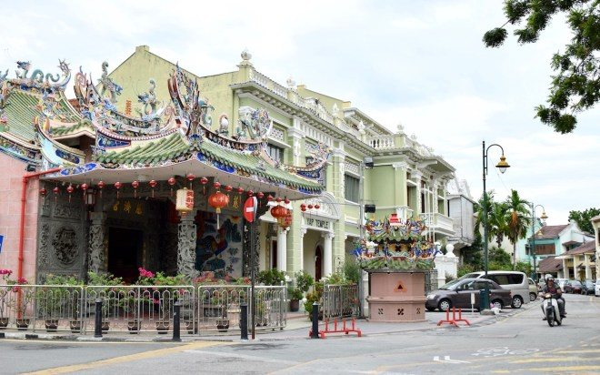 hellgrünes Haus im Kolonialstil mit chinesischem Tempel davor in Penang - Malaysia