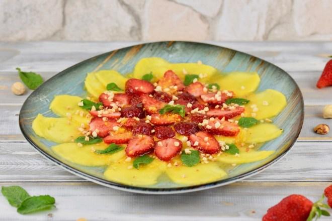 Erdbeer-Mango-Carpaccio mit Minze und Orangen-Dressing auf türkisem Teller garniert mit Minze und Haselnusskernen. Hintergrund weiß.