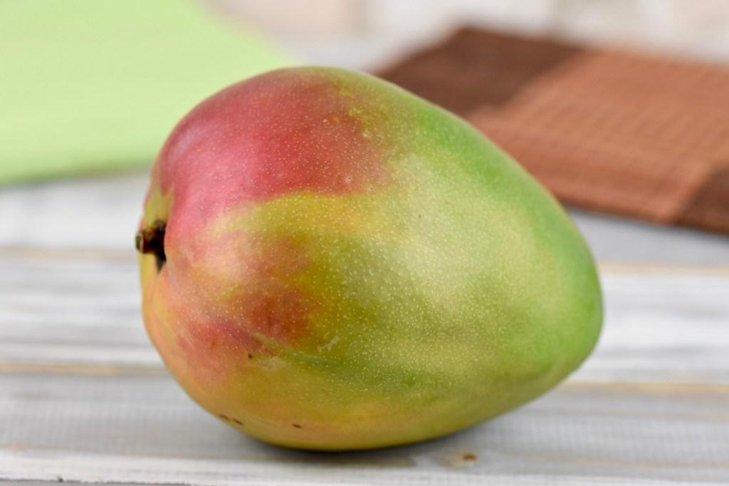 Mango auf hellem Holztisch.