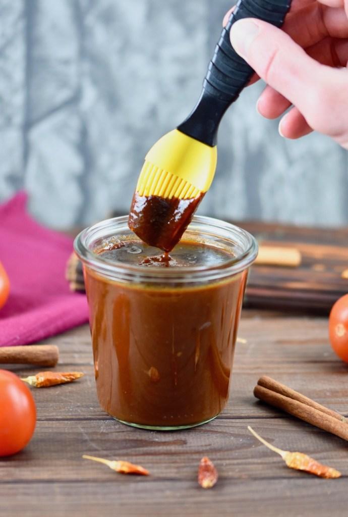 Rauchige BBQ-Sauce in einem Glas. Ein Pinsel mit gelben Silikonborsten wird in die Sauce getunkt. Hintergrund dunkel.