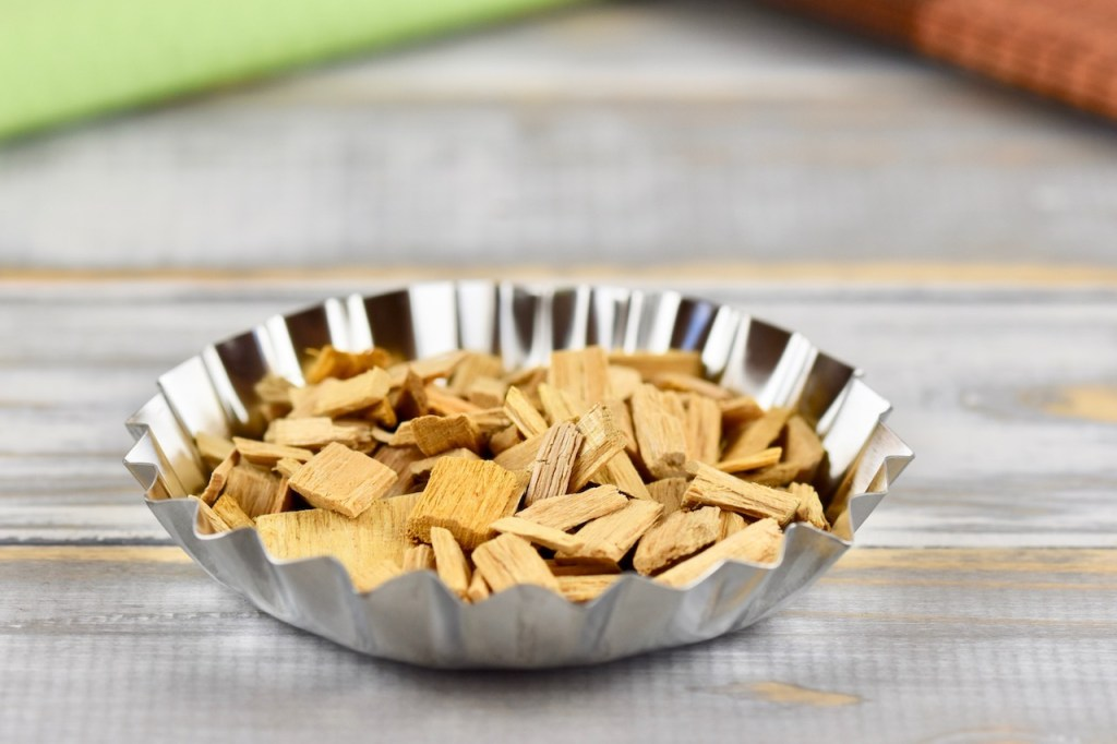 Muffinform aus Metall mit Räucher-Chips gefüllt. Hintergrund hell.