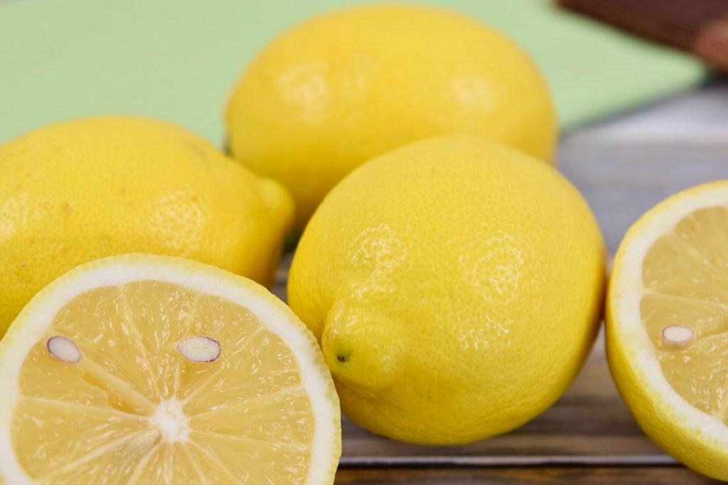 Mehrere Zitronen, eine ist aufgeschnitten. Hintergrund hell.