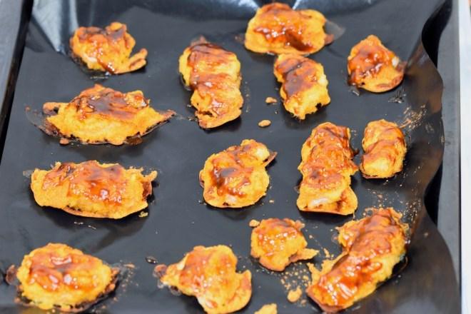 Hähnchennuggets im Teigmantel bestrichen mit Hoisin-Sauce auf einem Backblech.