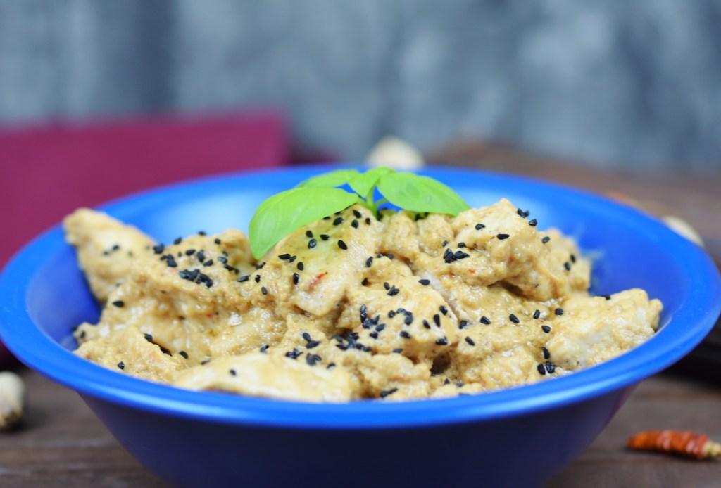 Hähnchen-Mezze in Tahini-Kokossauce in einer blauen Schale garniert mit Basilikum. Hintergrund dunkel.