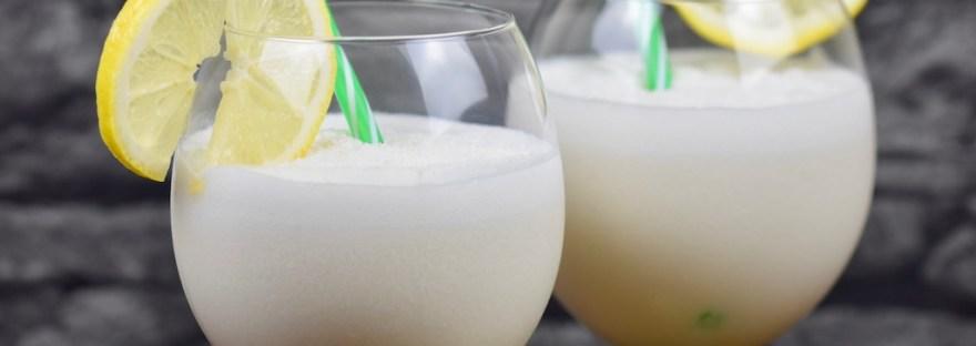 Tropische Kokoslimonade in zwei Weingläsern garniert mit einer Zitronenscheibe und einem Strohhalm. Hintergrund dunkel.