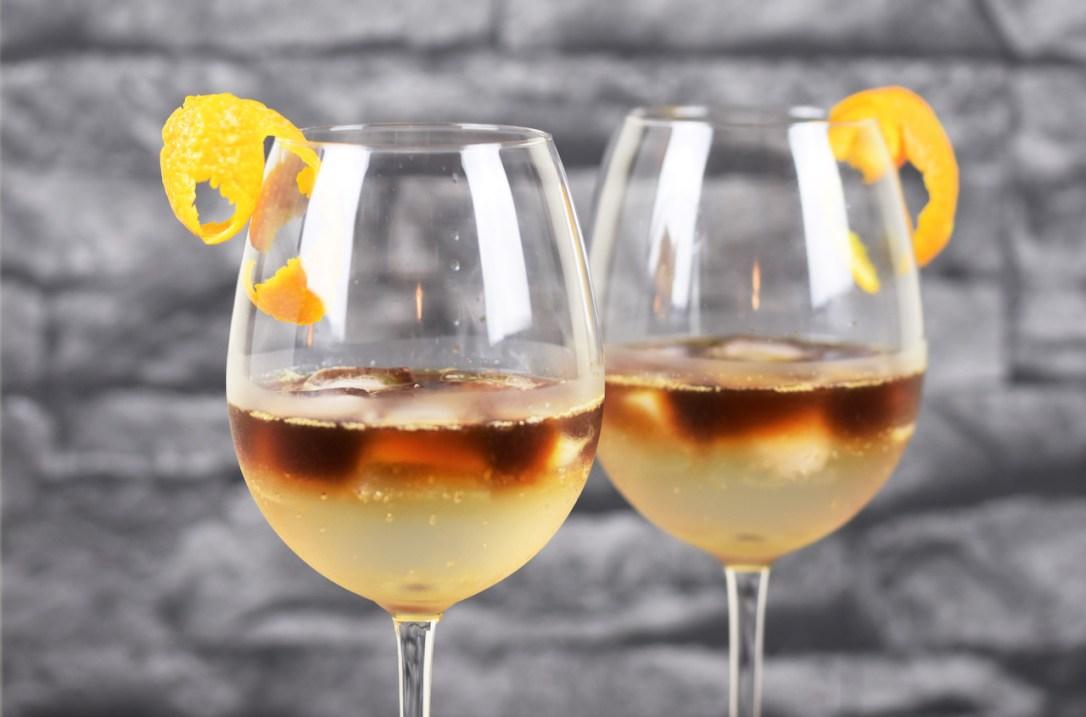 Zwei Espresso Tonic in Weingläsern. Hintergrund dunkel.
