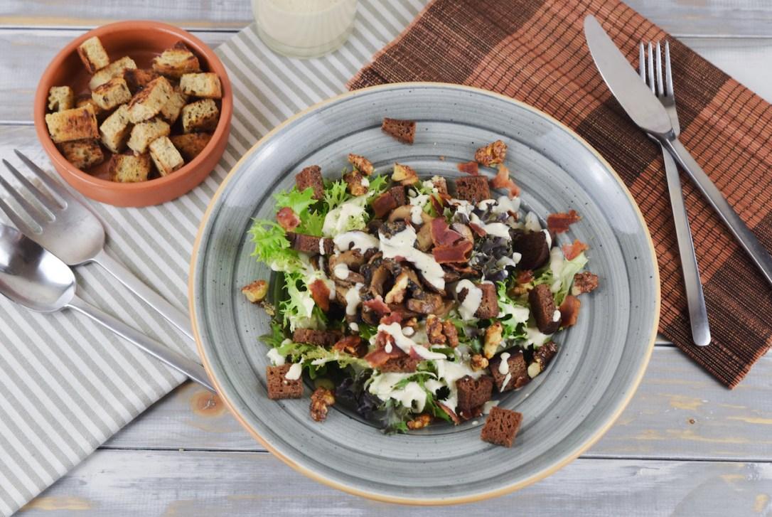 Veganer Caesar Salad mit Pilzen und Walnüssen auf grauem Teller. Hintergrund hell.
