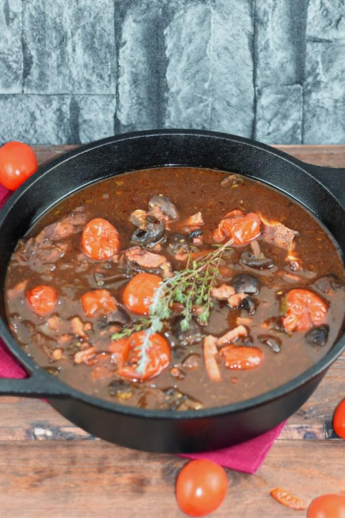 Coq au Vin aus dem Ofen in einem schwarzen Topf aus Gusseisen. Hintergrund dunkel.