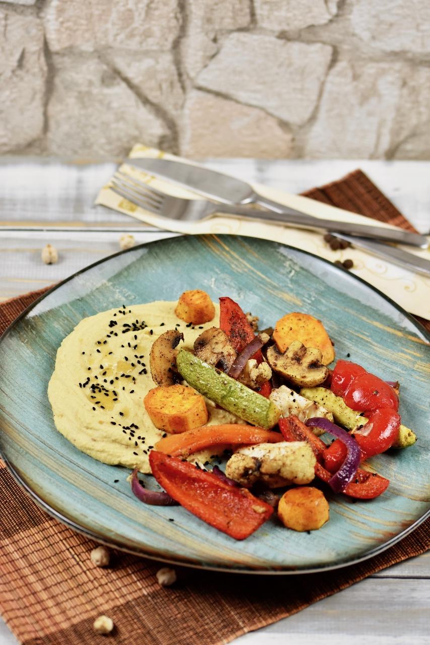Hummus mit geröstetem Knoblauch und Ofengemüse auf türkisem Teller.