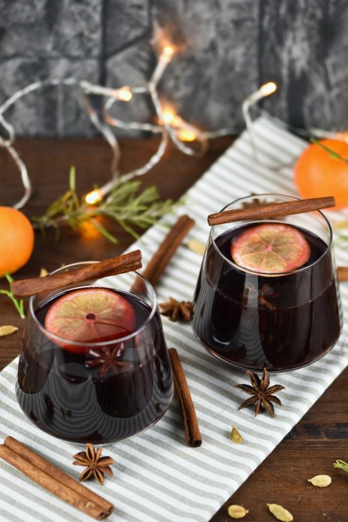 Klassischer Glühwein in 2 Gläsern auf hellem Tuch. Hintergrund dunkel.