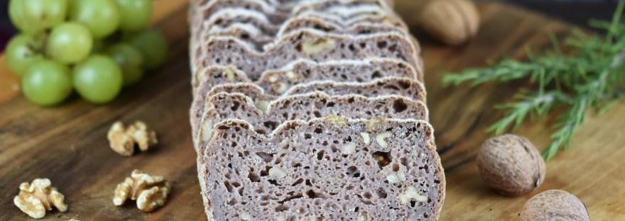 Glutenfreies Walnussbrot aufgeschnitten auf Holzbrett. Hintergrund dunkel.