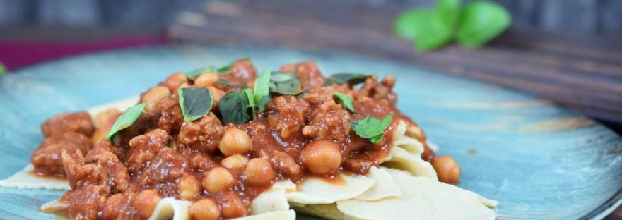 Pasta mit Salsiccia und Kichererbsen auf blauem Teller. Hintergrund dunkel.