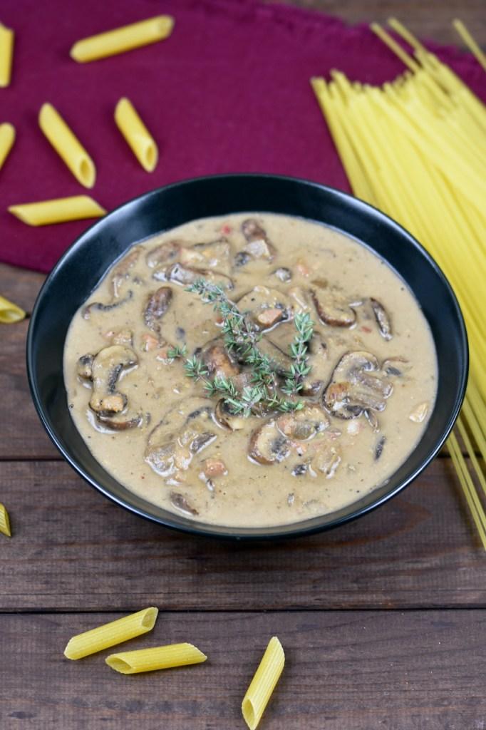 Cremige Pilzsauce aus Cashewkernen in einer schwarzen Schüssel. Drumherum liegen italienische Pasta. Hintergrund dunkel.
