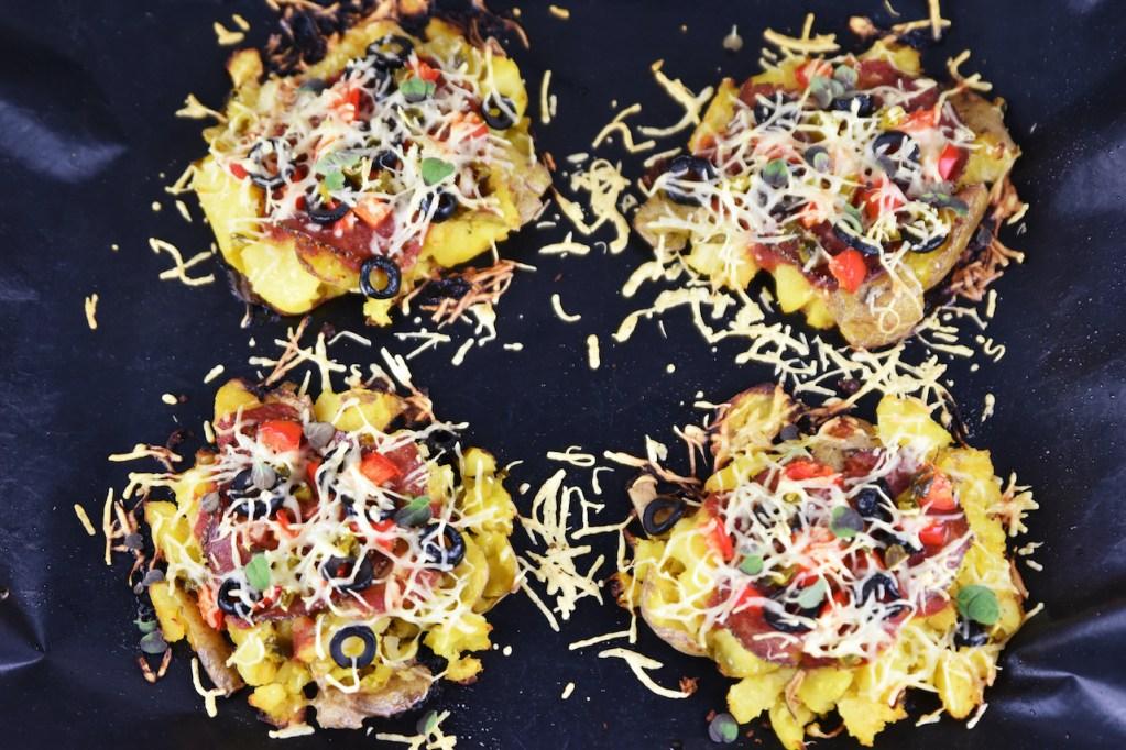 Pizza-Kartoffeln auf einem Backblech. Hintergrund dunkel.