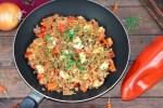 Schnelle Hackfleischpfanne mit Paprika und Feta in einer Pfanne. Hintergrund dunkel.