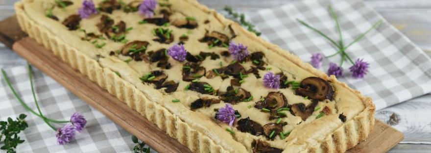 Längliche Quiche mit Lauch in Pilzen, garniert mit Schnittlauchblüten. Hintergrund hell.
